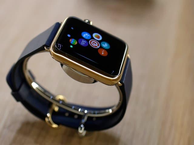 Eine Uhr mit einer Oberfläche ähnlich des iphones, präsentiert auf einem Tisch.