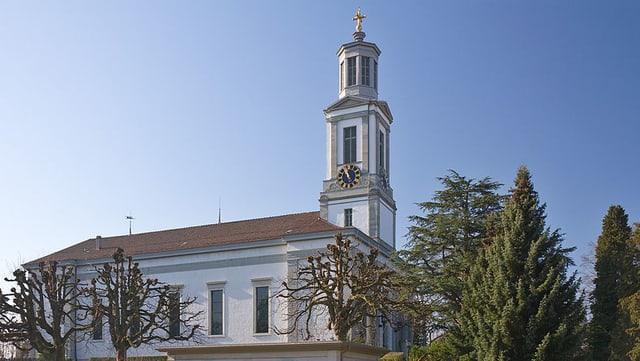 Die Kirche Neumünster mit dem spitzen Turm und dem goldenen Kreuz obendrauf.