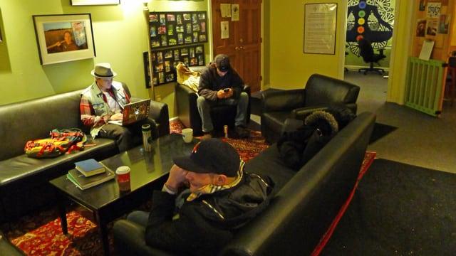 Drei junge Männer sitzen in einem Aufenthaltsraum im Portland Recovery Center.