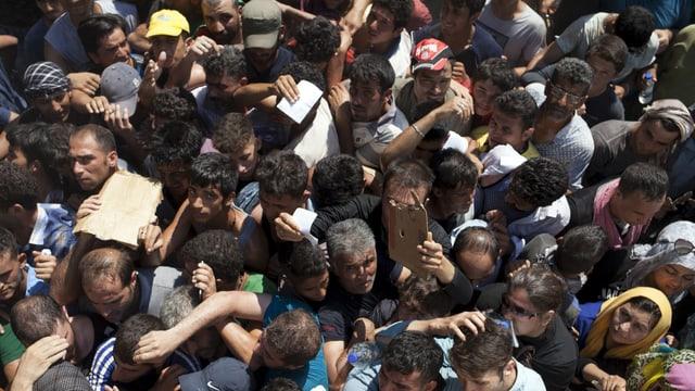Dutzende Migranten stehen dicht gedrängt in der Hitze