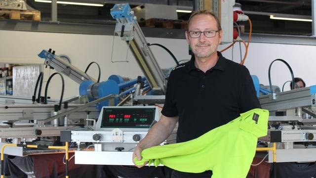 Tom Schütz mit einem hellgrünen Switcher-Shirt in seiner Firma Werk5