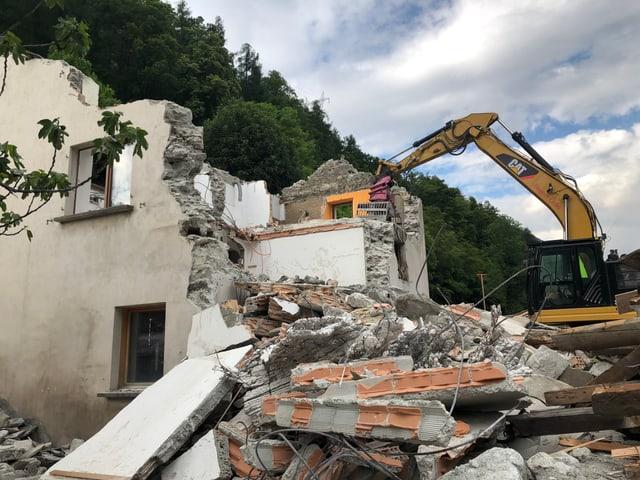 Ein zestörtes Haus und ein Bagger.