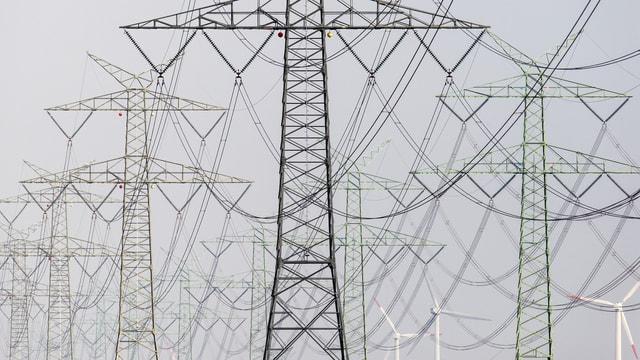 Strommasten und Windräder.