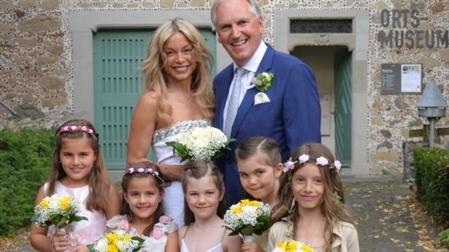 Thomas und Denise Borer mit Blumen und Blumenmädchen vor dem Standesamt.