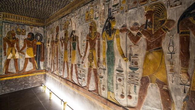 Wand mit bunten Reliefs ägyptischer Götter