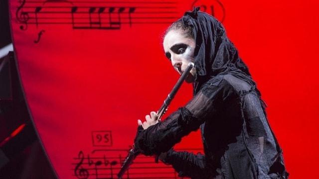 Ein Frau im schwarzen Kostüm spielt Querflöte.