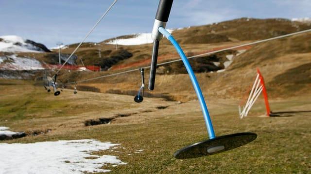 Ein Skilift-Teller im Vordergrund. Im Hintergrudn eine grüne Wiese mit etwas Schnee.