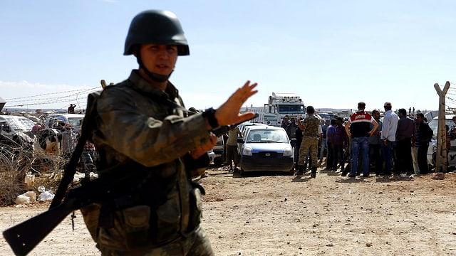 Türkischer Soldat, dahinter Flüchtlinge.