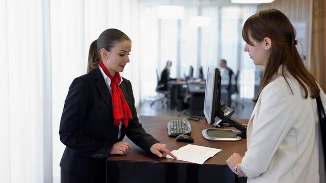 Bankangestellte bedient Frau an einem Schalter.
