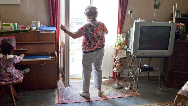 Alte Frau in bunter Bluse und grauer Hose öffnet in ihrer Stube das Balkonfenster.