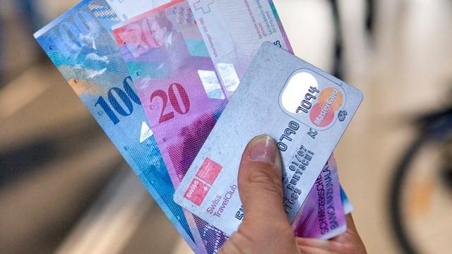 in maun che tegn duas bancnotas ed ina carta da credit