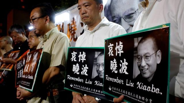 Männer stehen in einer Reihe, sie halten Plakate mit Fotos von Liu und chinesischem Text in ihren Händen.