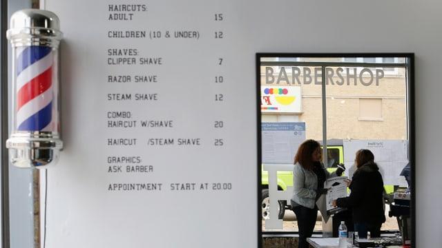 Ein Wahllokal, an dessen Wand die Preise für Haarschnitte aufgeführt sind.