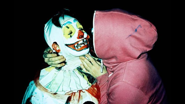 Figur mit Kaputzenpullover hält Clown fest.
