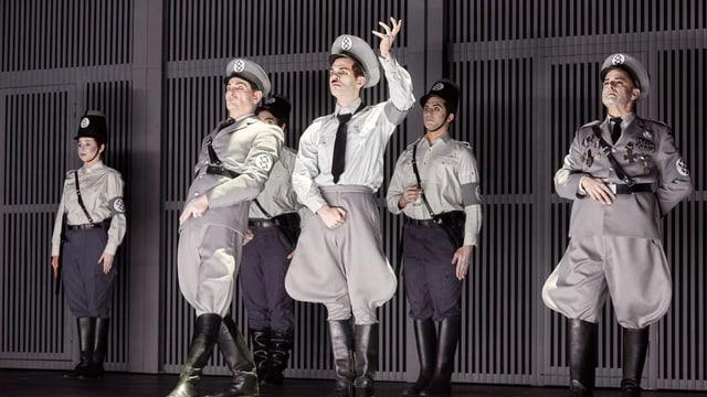 Bühne: Ein Mann mit Militärhut, Kravatte steckt seine linke Hand in die Höhe. Neben und hinter ihm stehen weitere Männer und Frauen, die ebenfalls in Militärbekleidung und schwarzen Stiefeln stramm stehen.