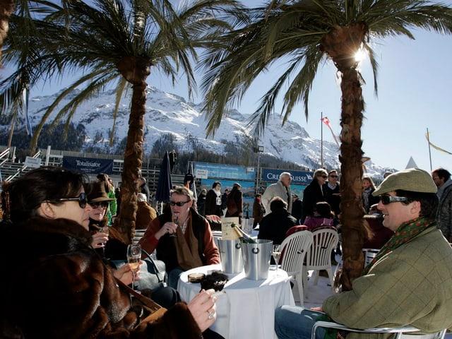 Menschen unter Palmen auf zugefrorenem See in St. Moritz