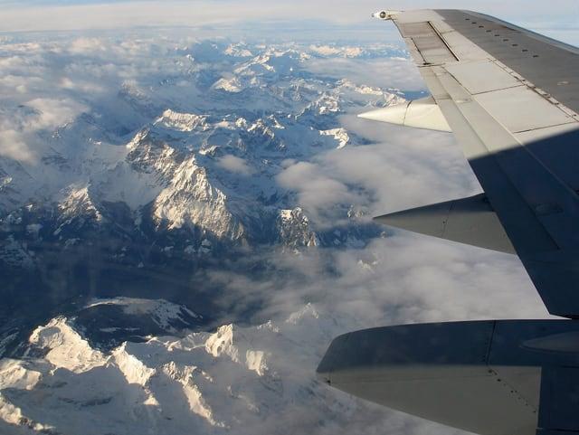 Blick aus dem Fenster eines Verkehrsflugzeuges auf die verschneiten Alpen aus grosser Höhe. Es hat auch einige Wolken. Rechts ist noch ein Teil des Flügels zu sehen.