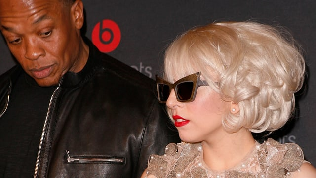Dr. Dre steht links neben Lady Gaga, die eine überdimensionierte Sonnenbrille trägt.