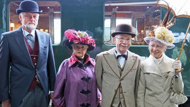 Vier Personen in historischen Gewändern vor einem BLS-Zug