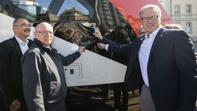 Zwei Männer weihen neuen Zug ein.