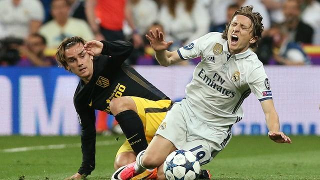 Antoine Griezmann und Luka Modric kämpfen um den Ball und sind dabei schon kniend auf dem Rasen.