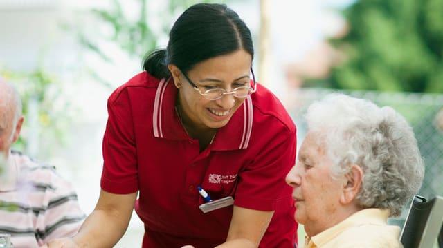 Eine Pflegerin wendet sich lächelnd einer Seniorin zu.