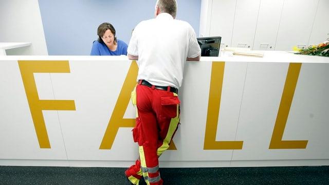 Ein Sanitäter steht an einer Empfangstheke mit der Aufschrift Notfall.