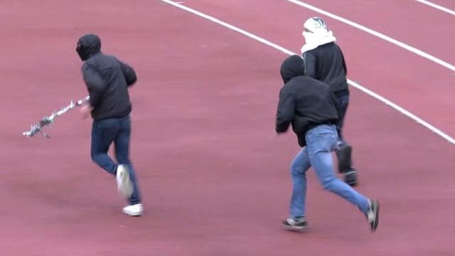 Hooligans rennen über die Tartanbahn im Fussballstadion.
