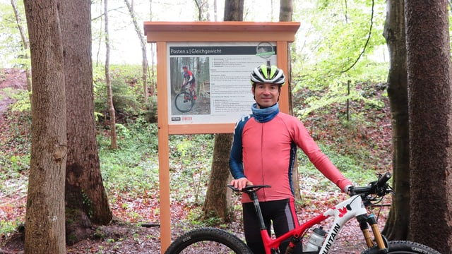 Ein Mann steht mit einem Mountainbike vor einer Infotafel eines Bikeparcours