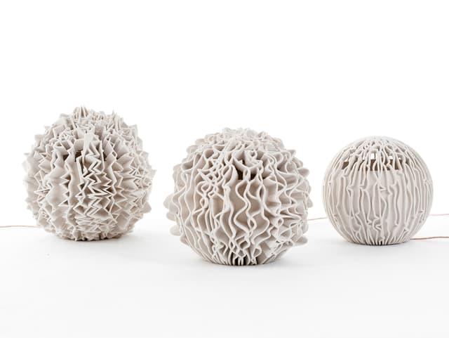 Kugelförmige Objekte mit gezakten Rillen vor weissem Hintergrund.