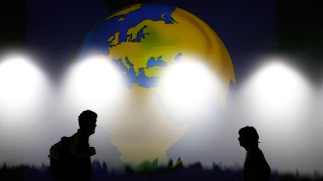 Zwei Menschen vor einem Globus
