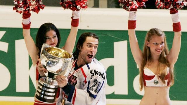 Zwei Cheerleader im Hintergrund, mit rotweissen Trikots, in deren Mitte der Eishockeyspieler Dvorak mit Pokal