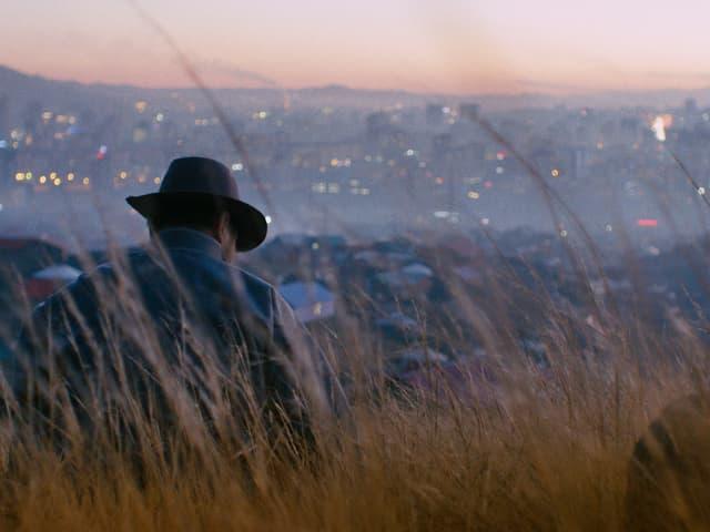 Ein Mann sitzt vor einer Stadt