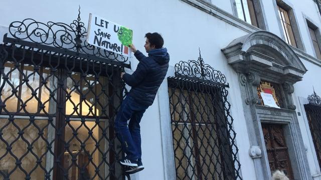 Mann hängt Plakat auf: Let us save nature