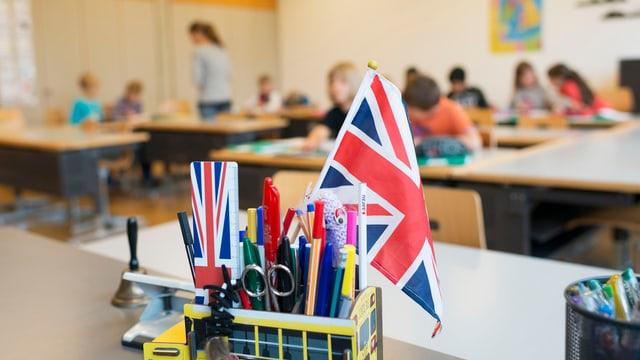 Ina stanza da scola e davant in recipient cun ina bandiera da la Gronda Britannia.