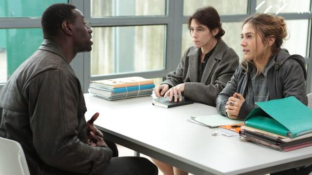 drei Menschen an einem Tisch