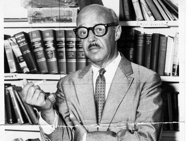 Nahaufnahme des Schriftstellers, der rauchend vor einem Bücherregal steht.