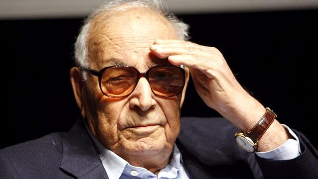 Ein Mann mit getönter Brille und Halbglatze, eine Hand über dem Auge.