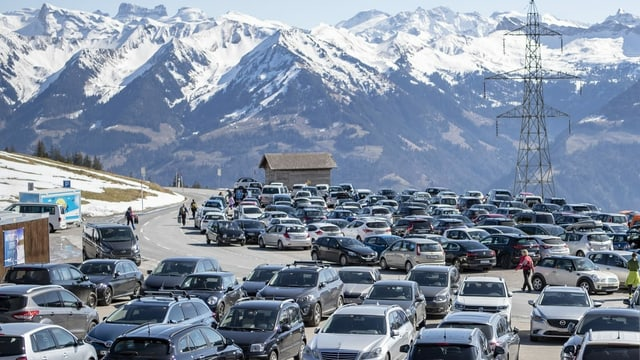 Zahlreiche Autos sind parkiert, im Hintergrund sieht man schneebedeckte Alpen.