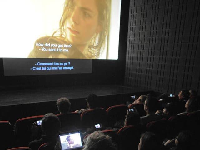 Im Kinosaal leuchten in allen Reihen die Bildschirme von Smartphones.