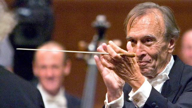 Abbado applaudiert mit Dirigentenstab in der Hand einem Musiker