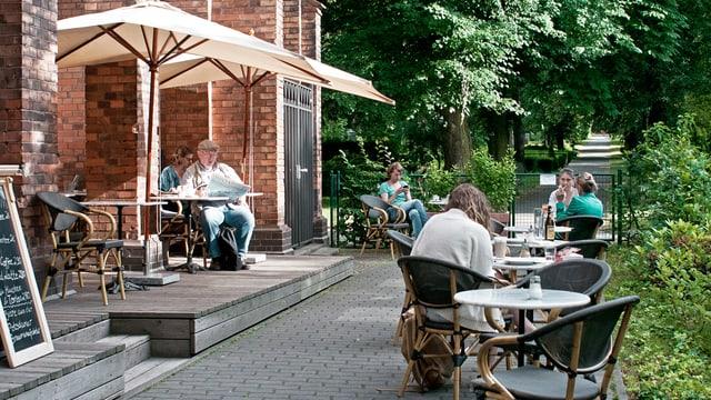 Leute sitzen an Tischen vor dem Café Strauss.