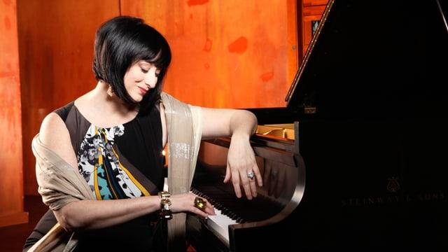 Eine dunkelhaarige Frau streichelt mit ihrer Rechten versonnen dia Tastatur eines Flügels.