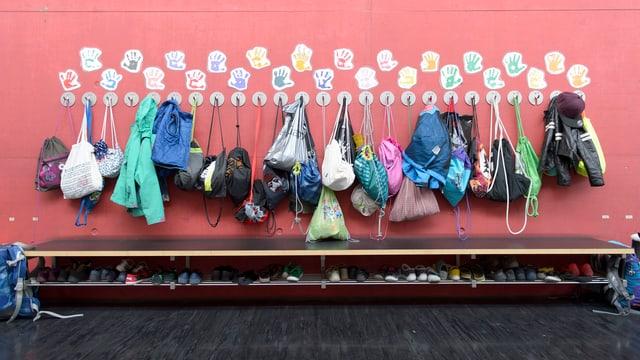 Schultaschen und Jacken hängen an einer roten Wand