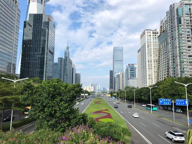 Blick in die Metropole mit Strassen und Hochäusern und einen blauen Himmel.