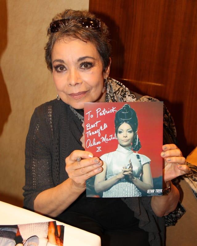 Arlene Martel streckt eine Autogramm-Karte in die Kamera