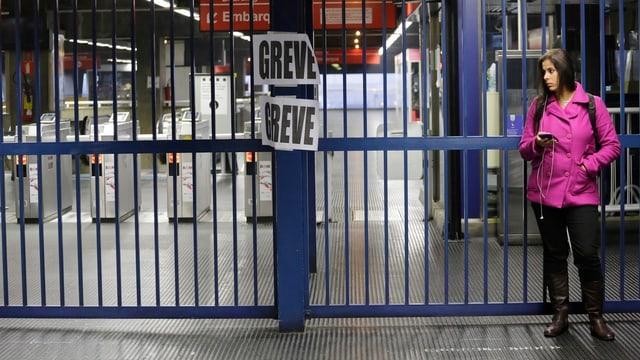 Eine Frau steht vor einem geschlossenen Gittertor auf dem zwei Schilder hängen: «Grève», also Streik.