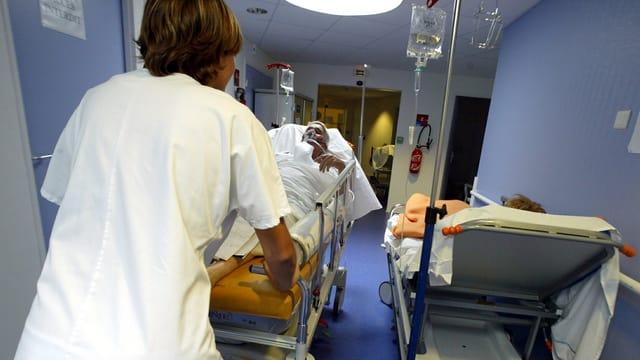 Eine Pflegefachfrau stösst ein Bett mit einem Patienten durch einen Spitalkorridor.