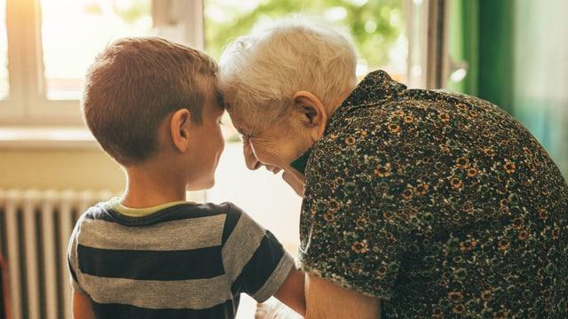 Eine alte Frau hält ein Knabe am Arm und lächelt.