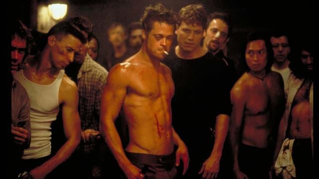 Ein Mann steht oben ohne vor einer Gruppe Männer in einem Keller. Sein Oberkörper ist blutverschmiert. Er raucht eine Zigarette.